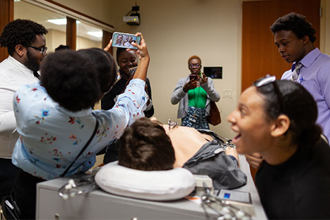 High school students in the Big Brothers Big Sisters School to Work program take a selfie with Harvey, the mannequin-based simulation tool.