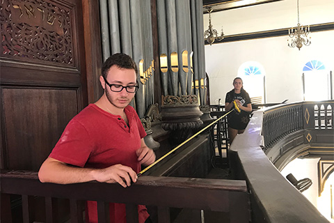 Joshua Kleinberg and Amanda Arrizabalaga measure the space in front of the 19th century organ.