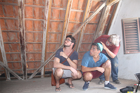 Professor Jorge Hernández points out attic features to Hector Valdivia Arrieta, left, and Hannan Vilchis-Zubizarreta, right.