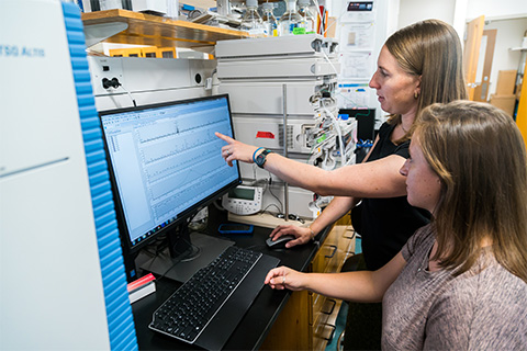 Assistant Professor of Ocean Sciences Kimberly Popendorf and graduate assistant Kaycie Lanpher review data from a liquid chromatography triple quadruple mass spectrometer used for toxin analysis.